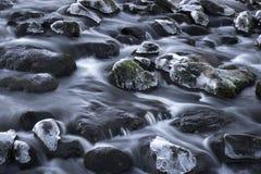 Rocce con ghiaccio nel flusso continuo dell'acqua Fotografie Stock