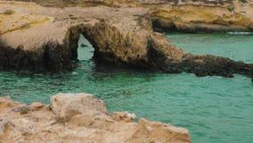 Rocce con il foro in bello mare ondulato blu, movimento lento archivi video