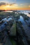 Rocce con muschio verde al tramonto Immagini Stock