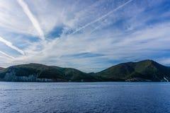 Rocce coperte dagli alberi sull'isola di Elba visibile dal mare Immagini Stock