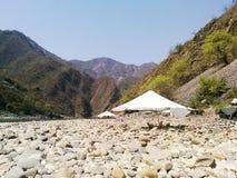 Rocce della riva del fiume con l'ombrello immagini stock