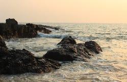 Rocce della spiaggia di Anjuna al tramonto immagini stock libere da diritti