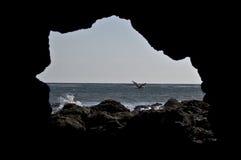 Rocce della spiaggia incorniciate in caverna Immagine Stock