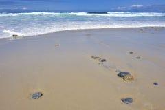 Rocce delle pietre delle onde di rotolamento sulla spiaggia vuota Fotografia Stock