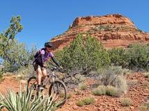 Rocce di ciclismo di montagna della donna in rosso, Sedona, U.S.A. fotografie stock libere da diritti