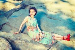 Rocce di seduta della giovane donna americana al Central Park, New York, con riferimento a Immagini Stock