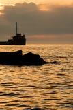 Rocce di Shoreline e un cargo di Grandi Laghi ad alba immagini stock