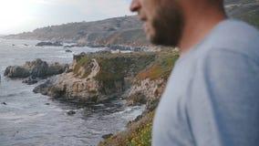 Rocce di stupore di sorveglianza della spiaggia dell'uomo al bello punto di vista della linea costiera dell'oceano del Big Sur su stock footage