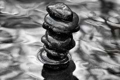 Rocce di zen del ` dell'impilatore del ` impilate in acqua con spese generali degli arti di albero immagini stock