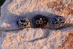 Rocce dipinte che dichiarano la sposa, faccio e sposo nel bianco sulle rocce nere Fotografia Stock