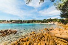 Rocce e gommone in una piccola baia in Sardegna immagini stock libere da diritti