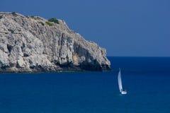 Rocce e piccola barca a vela Fotografia Stock