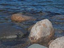 Rocce ed acqua ondulata blu Immagini Stock Libere da Diritti