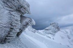 Rocce fantastiche misteriose congelate con ghiaccio e neve delle forme e delle strutture sconosciute di favole Tempo per le avven fotografia stock