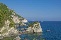 Rocce in Mar Ionio con la piccola chiesa e yacht nel fondo - Parga, Grecia fotografie stock