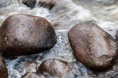Rocce nel fiume dell'acqua corrente Fotografie Stock