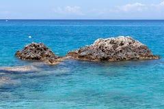 Rocce nelle acque blu del mare ionico, vicino al villaggio di Agios Nikitas fotografie stock libere da diritti