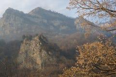 Rocce nelle montagne in una foschia nebbiosa con l'autunno, foglie dorate sugli alberi nella priorità alta Fotografia Stock Libera da Diritti