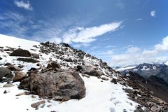 Rocce, neve, cielo e nubi in montagne Fotografia Stock