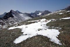Rocce, neve, nubi e cielo in montagne di Sayan. Sib Immagini Stock
