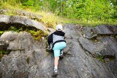 Rocce rampicanti del giovane ragazzo caucasico del bambino in foresta Fotografie Stock