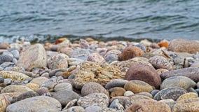 Rocce rosse, grige, gialle e blu sulla riva del lago Fotografia Stock