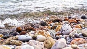 Rocce rosse, grige, gialle e blu sulla riva del lago Fotografie Stock
