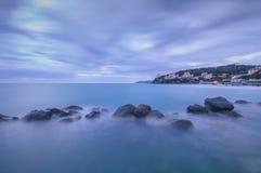 Rocce scure in un oceano blu su penombra. Castiglioncello, Italia immagine stock