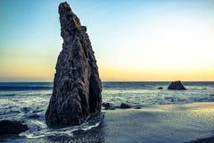 roccia al tramonto dall'oceano Fotografia Stock
