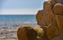 Roccia che somiglia ad una scimmia davanti al mare fotografie stock