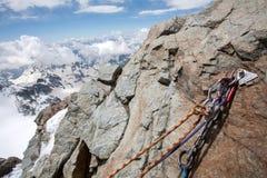 Roccia con la corda rampicante in priorità alta e le alpi nel fondo Fotografia Stock Libera da Diritti