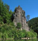 Roccia con un albero e un fiume immagine stock