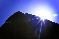 Roccia della colonna con i raggi del sole fotografia stock