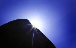 Roccia della colonna con i raggi del sole immagine stock