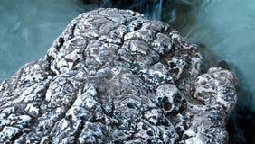 Roccia della spiaggia in chiaro mare blu fotografie stock