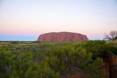 Roccia di Ayers, Australia al tramonto con i lotti di pianta Fotografie Stock