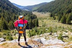 Roccia di condizione di viaggiatore con zaino e sacco a pelo sopra la valle Immagine Stock