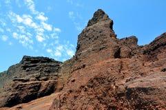 Roccia di terracotta e fondo del cielo blu La spiaggia rossa famosa nell'isola di Santorini, Grecia Fotografia Stock