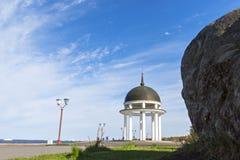 Roccia e rotunda sulla banchina del lago della città Immagine Stock