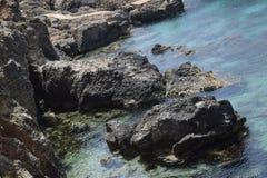 Roccia nera nel mar Mediterraneo blu fotografia stock libera da diritti