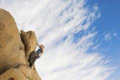 Roccia rampicante della ragazza contro il cielo nuvoloso Fotografia Stock Libera da Diritti