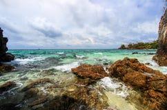 Roccia sbalorditiva su una riva con fondo nuvoloso Fotografie Stock