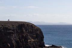 Roccia scenica che trascura il mare Ciclista su un fondo del cielo e della pietra, spiaggia Lanzarote di Papagayo Fotografie Stock Libere da Diritti