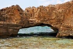 Roccia scenica dell'arco in acqua di mare Immagini Stock