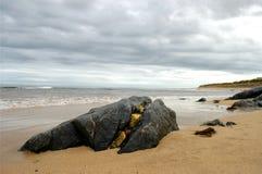 Roccia spaccata sulla spiaggia immagini stock