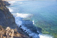 Roccia vigorosa, crolli in un mare blu, con abbagliamento del sole, rocce maestose Immagine Stock