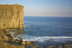 Roccia vigorosa, crolli in un mare blu, con abbagliamento del sole, rocce maestose Immagine Stock Libera da Diritti
