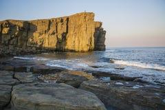 Roccia vigorosa, crolli in un mare blu, con abbagliamento del sole, rocce maestose Fotografie Stock Libere da Diritti