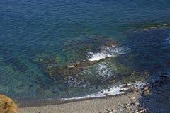Roccia vigorosa, crolli in un mare blu, con abbagliamento del sole, rocce maestose Fotografia Stock