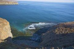Roccia vigorosa, crolli in un mare blu, con abbagliamento del sole, rocce maestose Immagini Stock Libere da Diritti